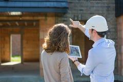 Молодая женщина и архитектор на строительной площадке стоковые изображения rf