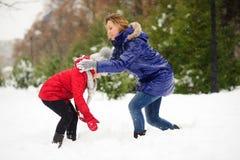 Молодая женщина и девушка ваяют снеговик Стоковая Фотография