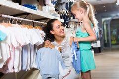 Молодая женщина и девушка в магазине одежд Стоковое фото RF