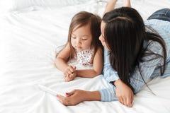 Молодая женщина и ее маленькая дочь смотря мобильный телефон Стоковое фото RF
