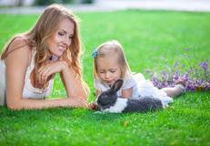 Молодая женщина и ее дочь играя с кроликом любимчика в парке стоковая фотография