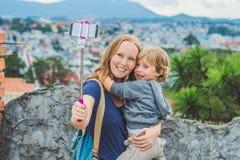 Молодая женщина и ее сын принимая умным изображениям автопортрета телефона с selfie stickon предпосылку города Dalat, Вьетнама Стоковое Фото