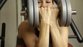 Молодая женщина идет внутри для спорт, фитнеса на спортзале девушка держа гантели и делая тренировки сток-видео