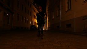Молодая женщина идет через темные улицы старого городка в Европе latvia riga акции видеоматериалы