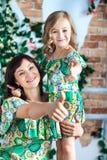Молодая женщина и маленькая девочка в ярких платьях показывают большие пальцы руки-вверх Мама и дочь Стоковые Фотографии RF