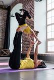 Молодая женщина и маленькая девочка делая летание йоги партнера представляют работать совместно стоковые изображения