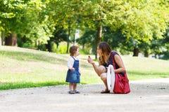 Молодая женщина и маленькая девочка одного года идя до лето p Стоковое Фото