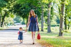 Молодая женщина и маленькая девочка одного года идя до лето p Стоковые Фото
