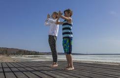Молодая женщина и мальчик делая Salutation к Солнцю Стоковое Изображение RF