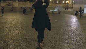 Молодая женщина идя в город вечера самостоятельно Привлекательная женщина ждать кто-нибудь в центре города, на квадрате видеоматериал