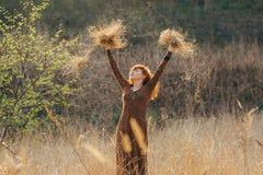 Молодая женщина идя в золотое поле высушенной травы Стоковое фото RF