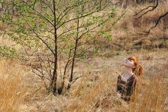 Молодая женщина идя в золотое поле высушенной травы Стоковые Изображения RF