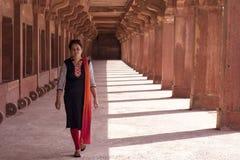 Молодая женщина идя в дорожку колоннады Стоковые Фото