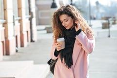 Молодая женщина идя в солнечный город Стоковые Фото