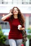 Молодая женщина идя и говоря на мобильном телефоне Стоковое Изображение