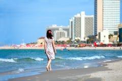 Молодая женщина идя на пляж стоковое изображение