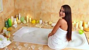 Молодая женщина идя принять ванну в ее ванной комнате сток-видео