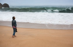 Молодая женщина идя самостоятельно на дезертированное побережье Атлантики Стоковое Фото