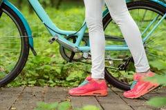Молодая женщина идя с велосипедом в парке Стоковое Фото