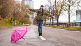 Молодая женщина идя с зонтиком в осени ненастной Стоковые Изображения RF