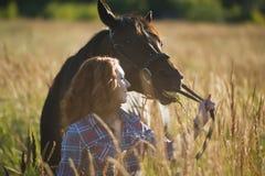 Молодая женщина идя с лошадью в луге на летнем дне Стоковое Изображение RF