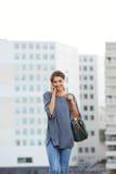 Молодая женщина идя outdoors и говоря на сотовом телефоне Стоковое фото RF
