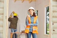 Молодая женщина как ремесленник держа большие пальцы руки вверх Стоковые Фото
