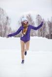 Молодая женщина катаясь на коньках на льде с диаграммой коньками Стоковые Фотографии RF