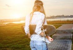Молодая женщина конькобежца на заходе солнца Женщина с Стоковая Фотография RF
