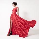 Молодая женщина красоты в порхая красном платье. Белая предпосылка. стоковое фото