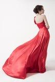 Молодая женщина красоты в порхая красном платье. Белая предпосылка. стоковые изображения
