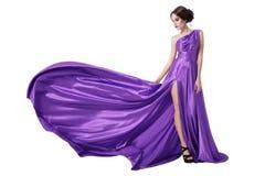 Молодая женщина красоты в порхая фиолетовом платье. Изолированный стоковое изображение
