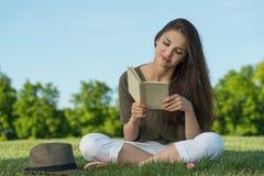 Молодая женщина красоты с книгой в парке Стоковые Фото