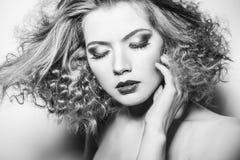 Молодая женщина красоты с курчавыми большими и длинными permed волосами стоковое изображение rf