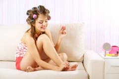 Молодая женщина крася ее ногти Стоковая Фотография