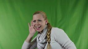 Молодая женщина крича и слушая. видеоматериал