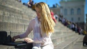 Молодая женщина кладет в сторону компьтер-книжку и выбирает вверх книгу на лестницах в центре города, замедленного движения акции видеоматериалы