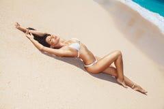 Молодая женщина кладет на тропический пляж Стоковое Фото