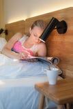 Молодая женщина кладя в кровать читая кассету Стоковая Фотография