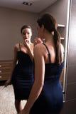 Молодая женщина кладя на губную помаду перед зеркалом Стоковая Фотография