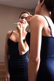 Молодая женщина кладя на губную помаду перед зеркалом Стоковое Изображение