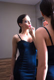 Молодая женщина кладя на губную помаду перед зеркалом Стоковая Фотография RF