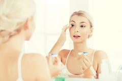 Молодая женщина кладя на контактные линзы на ванной комнате Стоковое Изображение