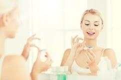 Молодая женщина кладя на контактные линзы на ванной комнате Стоковые Изображения RF