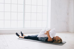 Молодая женщина кладя на циновку с подушкой стоковое фото rf