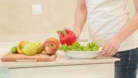 Молодая женщина кладя овощи на плиту органическо видеоматериал