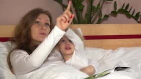 Молодая женщина матери показывая звезды на потолке к ее прелестной девушке ребенка акции видеоматериалы