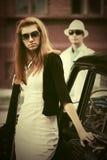 Молодая женщина моды в солнечных очках рядом с винтажным автомобилем Стоковое Фото