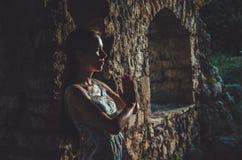 Молодая женщина моля в крепости бара Stari старой, Черногории Силуэт девушки на заходе солнца Вероисповедание, размышляя, духовно Стоковое Фото