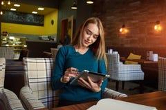 Молодая женщина наблюдает видео на цифровой таблетке во время остатков в современной кофейне стоковые фотографии rf